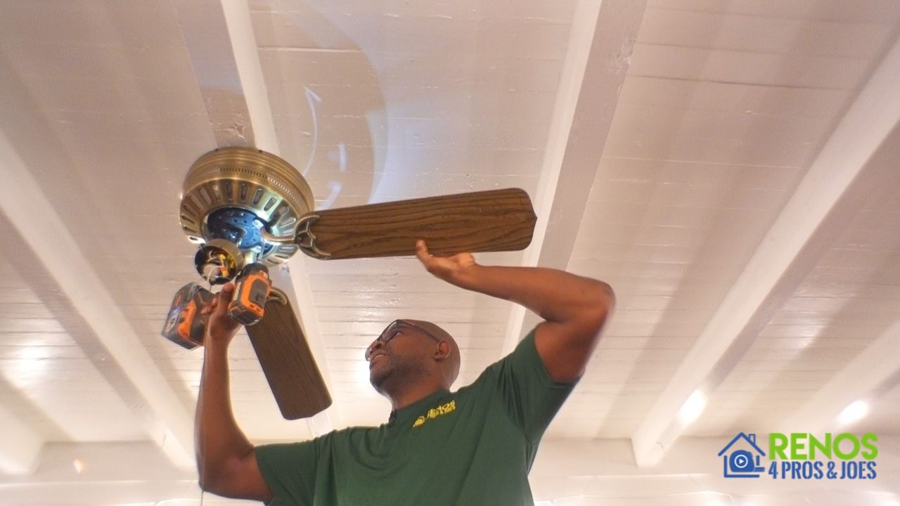 man removing an old ceiling fan